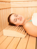 Smiling woman lying on bench at sauna — Stock Photo