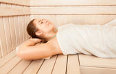 Beautiful woman lying on bench at sauna — Stock Photo