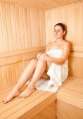 Brunette woman sitting on bench at wooden traditional sauna — Stock Photo