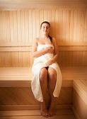 Young woman in towel relaxing at sauna — Stock Photo