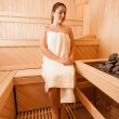 Woman sitting on bench next to sauna oven — Stock Photo