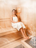 Woman in towel relaxing on bench at steamed sauna — Stock Photo