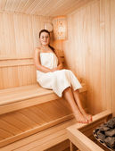 Woman in towel sitting on bench at sauna next to oven — Foto Stock