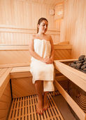 Woman sitting on bench next to sauna oven — Foto de Stock