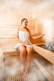 Woman sitting in steamed sauna next to oven — Stock Photo