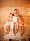 Woman with little girls relaxing at finnish sauna — Stock Photo