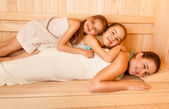 Little girls lying on mothers back at sauna — Stock Photo