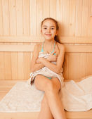 Smiling little girl sitting on bench at sauna — Stock Photo