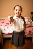 Portrait of smiling schoolgirl holding red pencil — Stock Photo