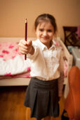 Little schoolgirl holding red pencil — Stock Photo