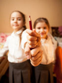 Two little sisters holding red pencil — Stock Photo