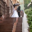 Ust married couple kissing on stairway at rain — Stock Photo #43707407
