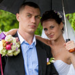 Just married couple hugging under umbrella — Stock Photo