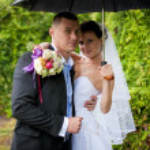 Portrait of happy bride and groom standing under umbrella — Stock Photo