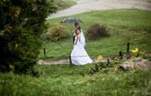 Bride and groom walking at park on rainy day — Photo