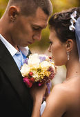 Portrait of bride and groom holding bouquet — Stock Photo