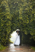 Newly married couple dancing at tunnel in trees — Stock Photo
