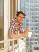 Portrait of hipster guy drinking coffee on balcony — Stock Photo