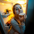 Portrait of woman biting donut at night near fridge — Stock Photo #44227863