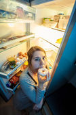Woman in pajamas eating donut next to refrigerator — Stock Photo