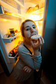 Portrait of woman biting donut at night near fridge — Stock Photo