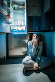 Woman in pajamas eating on floor next to fridge at night — Stock Photo