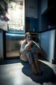 young woman eating next to refrigerator at night — Stock Photo
