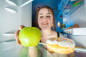 Portrait from inside the fridge of woman taking apple — Stock Photo