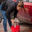 Young woman wringing rag while washing car outdoor — Stock Photo #44300573