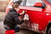 Woman cleaning car door from mud and dirt — Stock Photo