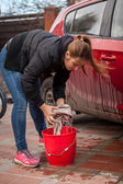 Young woman wringing rag while washing car outdoor — Foto Stock