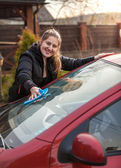 Portrait of woman washing car windscreen — Stock Photo