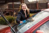 Smiling woman washing car windscreen at yard — Stock Photo