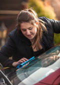 Young woman polishing windscreen — Stock Photo