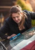 Young woman polishing windscreen — Stock Photo