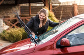 Beautiful woman washing car windscreen — Stock Photo