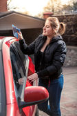 Smiling woman polishing car with rag — Stock Photo