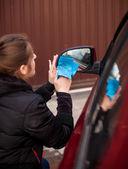 Портрет женщины, очистка зеркало автомобиля — Стоковое фото