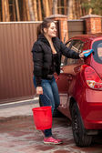 Young woman washing her small red car  — Stock Photo