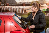 Portrait of brunette woman washing red car outdoor — Stock Photo