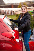 Smiling woman washing red car at backyard — Stock Photo
