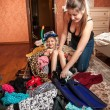 Mother packing clothes and daughter in tourist suitcase — Stock Photo