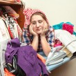 Tired housewife in pile of not ironed clothes — Stock Photo