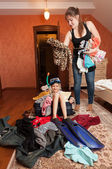Girl sitting in suitcase while woman throwing clothes in it — Stock Photo