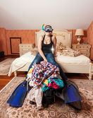 Woman in flippers and mask sitting on packed suitcase — Stock Photo