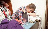 Vyčerpaná žena žehlení velkou hromadu oblečení — Stock fotografie