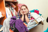 Tired housewife in pile of not ironed clothes — Stockfoto
