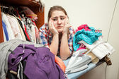 Sad woman leaning against huge pile of not ironed clothes — Stock Photo