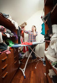 Housewife looking at not ironed clothes at wardrobe — Stock Photo