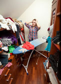 Housewife having headache of big pile of not ironed clothes — Stock Photo
